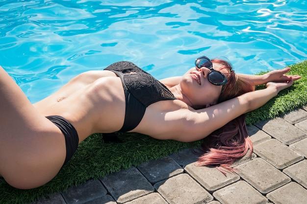 Bela garota sexy jovem com corpo esguio perfeito com cabelo longo molhado em biquíni e óculos escuros, sentado na piscina. modelo feminino de cabelo comprido lindo posando à beira da piscina, um retrato ao ar livre.