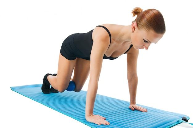 Bela garota vermelha exercitando com bola e esteira de ioga