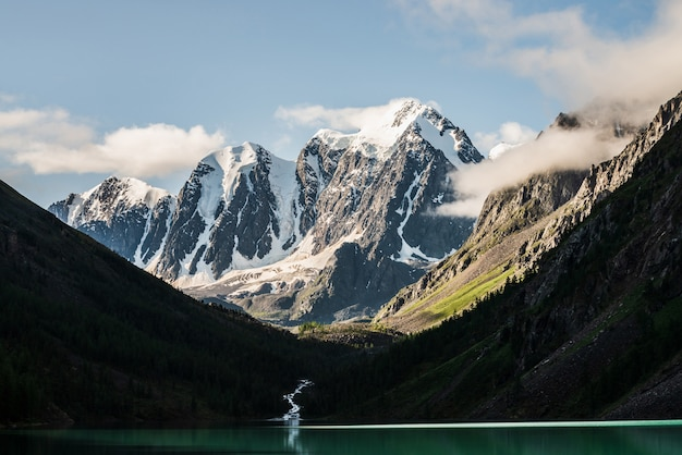 Bela grande geleira, montanhas rochosas nevadas, floresta de coníferas nas colinas, lago de montanha e riacho das terras altas sob o céu azul com nuvens.