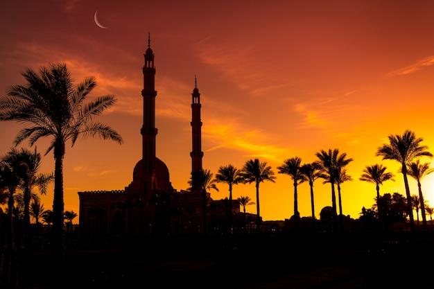 Bela grande mesquita islâmica no fundo do céu ao pôr do sol
