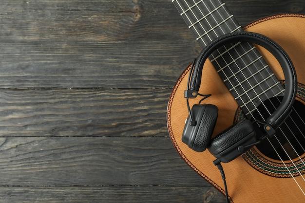 Bela guitarra clássica com fones de ouvido na mesa de madeira