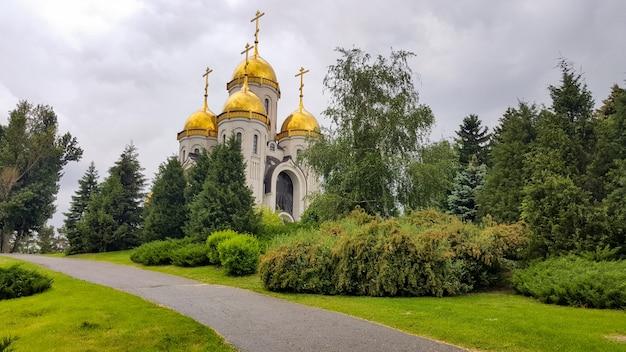 Bela igreja cristã com cúpulas douradas entre árvores verdes