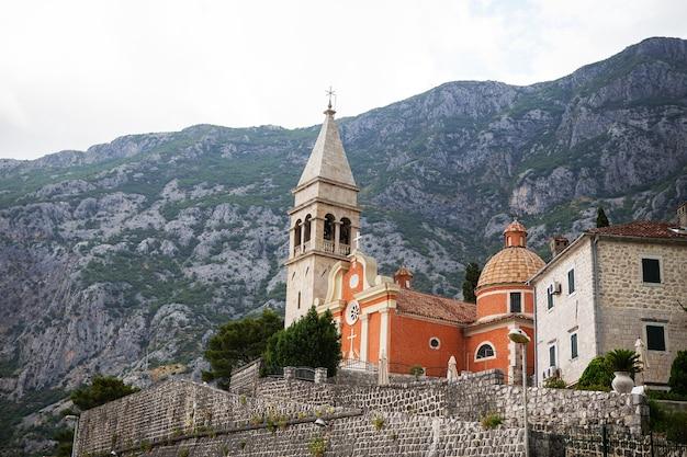 Bela igreja em um fundo de montanhas na cidade velha de kotor, montenegro.