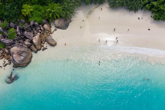 Bela ilha nas seychelles. la digue, praia de anse d'argent. água que flui e ondas espuma em uma paisagem tropical