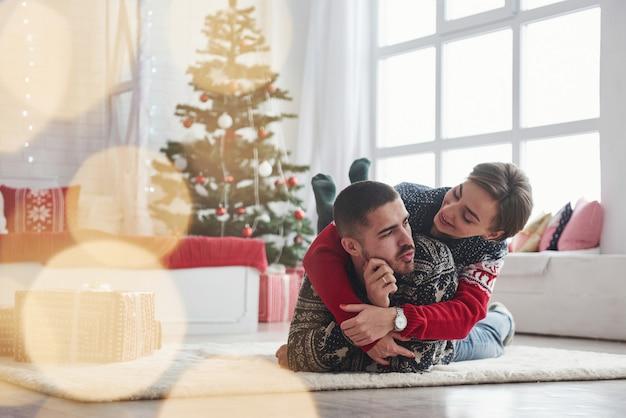 Bela iluminação e excelente ambiente. lindo casal jovem deitado na sala de estar com a árvore verde férias no fundo