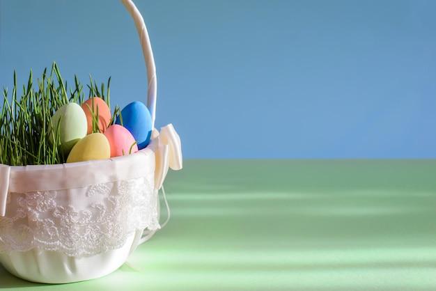 Bela imagem brilhante com ovos de páscoa na cesta em fundo azul esverdeado com espaço de cópia