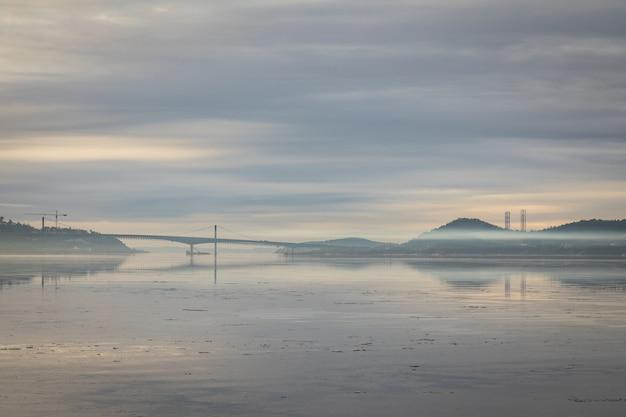 Bela imagem do nevoeiro sobre o fiorde em kristiansand, com a ponte varodd