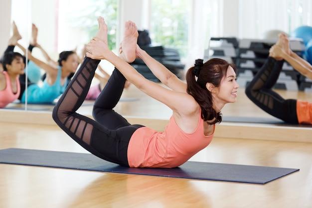 Bela ioga desportiva e ioga praticam yoga asana dhanurasana