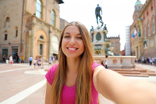 Bela italia. mulher jovem sorridente atraente tirar auto-retrato na piazza del nettuno quadrado cidade de bolonha, itália.