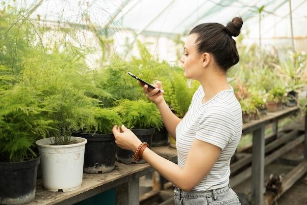 Bela jardineira adolescente em roupa casual tira fotos de plantas no telefone para blog