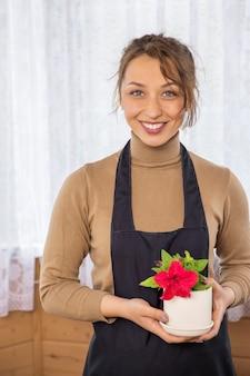 Bela jardineira segura um vaso de cerâmica com petúnias vermelhas florescendo nas mãos, foco no florista, jovem empresária feliz cultivando flores, horta, hobby de jardinagem, floricultura, pequena empresa