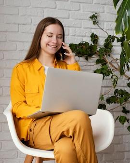 Bela jardineira trabalhando em seu laptop