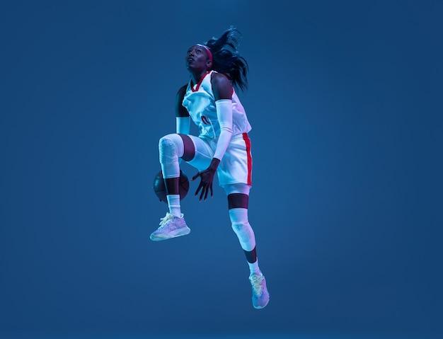 Bela jogadora de basquete afro-americana em movimento e ação em luz de néon na parede azul conceito de passatempo de esporte profissional estilo de vida saudável