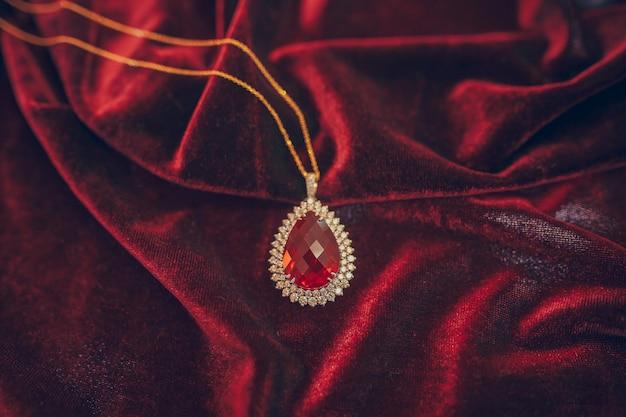 Bela jóia de ouro com jem no fundo de veludo vermelho