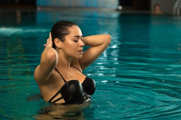 Bela jovem a nadar na piscina no centro de spa