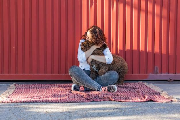 Bela jovem abraçando seu cachorro, um cão de água marrom espanhol