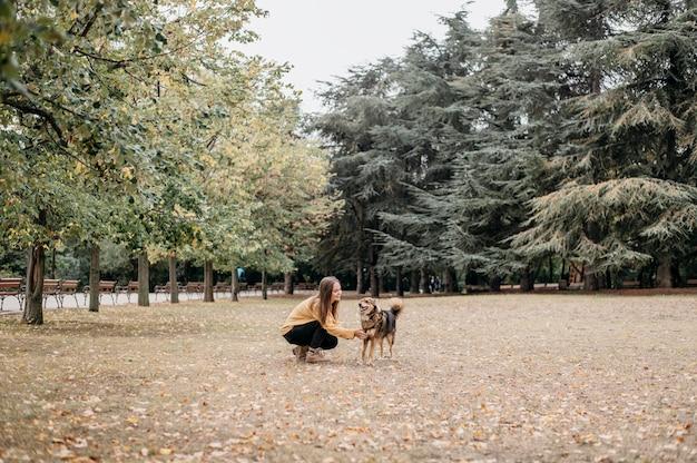 Bela jovem acariciando seu cachorro
