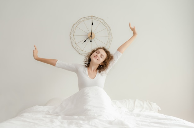 Bela jovem acordando e estendendo-se em sua cama de manhã