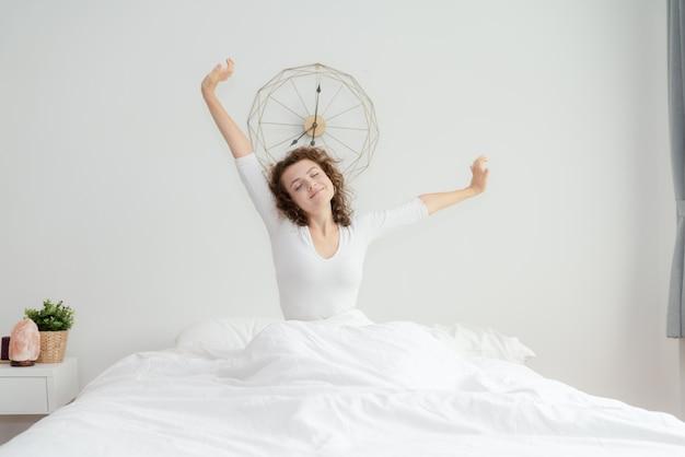 Bela jovem acordar e esticar em sua cama de manhã