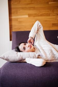 Bela jovem acordou depois de uma soneca diária entre o trabalho a fazer no sofá escuro no apartamento à moda