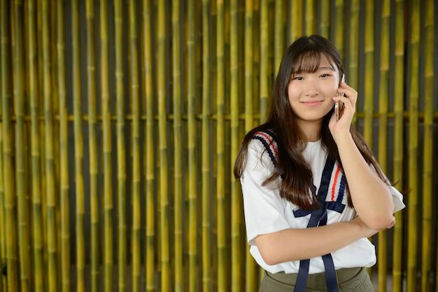 Bela jovem adolescente asiática falando ao telefone contra uma cerca de bambu