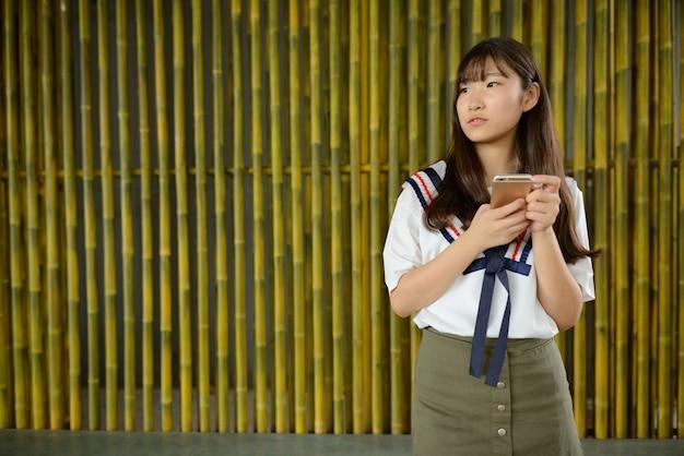 Bela jovem adolescente asiática pensando enquanto usa o telefone contra uma cerca de bambu