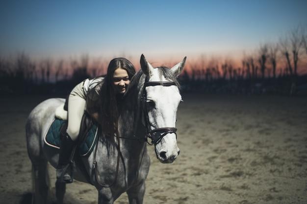 Bela jovem adolescente cavalgando um cavalo branco ao pôr do sol.