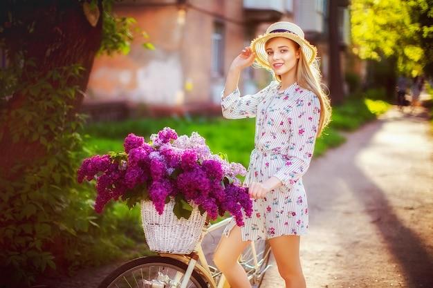 Bela jovem adolescente com bicicleta vintage e flores na cidade à luz do sol ao ar livre.