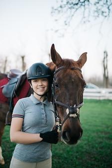 Bela jovem adolescente curtindo com seu cavalo. foco seletivo no olho do cavalo.