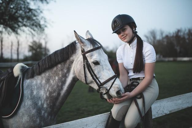 Bela jovem adolescente desfrutando com seu cavalo no rancho. foco seletivo no cavalo.