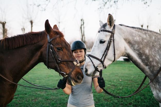 Bela jovem adolescente desfrutando com seus cavalos no rancho. foco seletivo na garota.