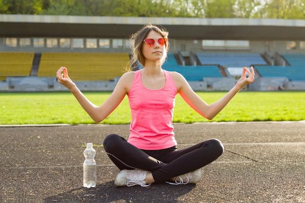 Bela jovem adolescente praticando ioga