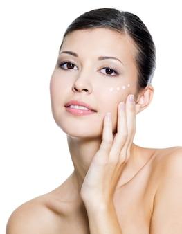 Bela jovem adulta aplicando creme cosmético ao redor do olho