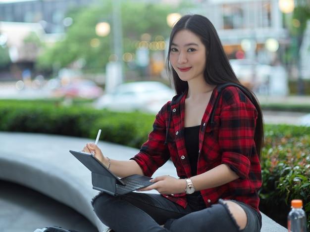 Bela jovem adulta com tablet e caneta stylus nas mãos, sentada no parque da cidade perto da rua