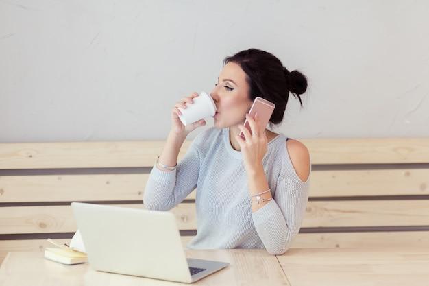Bela jovem adulta com telefone celular enquanto trabalha no laptop na mesa ao lado da xícara de café