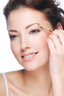 Bela jovem adulta desenha o formato da beleza das sobrancelhas usando uma escova cosmética.