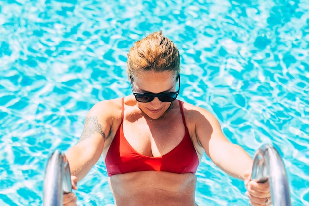 Bela jovem adulta na piscina com biquíni vermelho e água azul