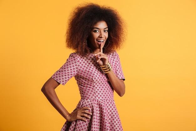 Bela jovem africana com penteado afro, mostrando o gesto de silêncio
