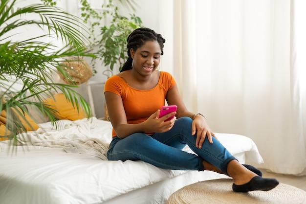 Bela jovem africana com telefone celular no interior, sentada na cama no quarto