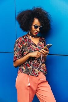 Bela jovem africana em óculos escuros e fones de ouvido, usando um smartphone