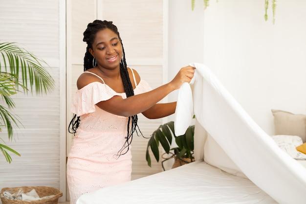 Bela jovem africana fazendo cama no quarto