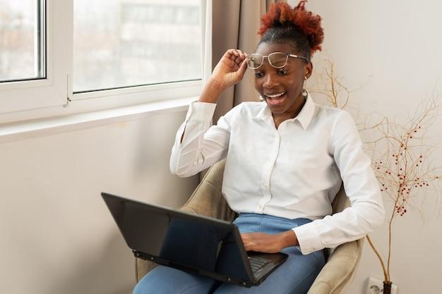 Bela jovem africana sentada com um laptop dentro de casa perto da janela com uma cara surpresa