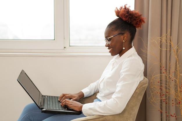 Bela jovem africana sentada com um laptop dentro de casa perto da janela
