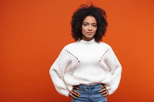 Bela jovem africana sorridente, vestindo um suéter em pé, isolado na parede vermelha, com as mãos nos quadris