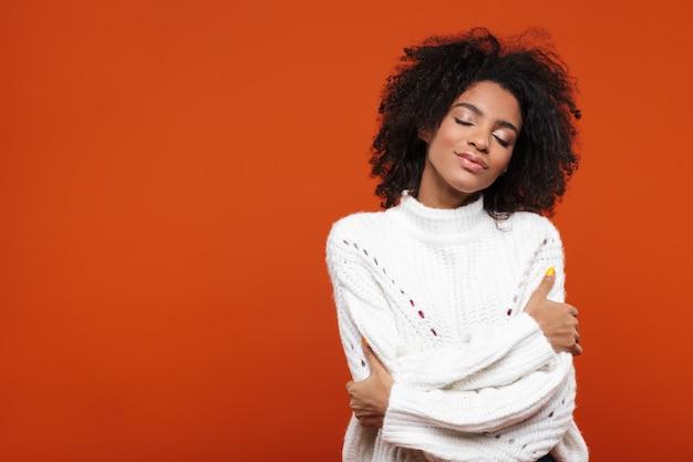 Bela jovem africana sorridente, vestindo um suéter em pé sobre uma parede vermelha, olhos fechados