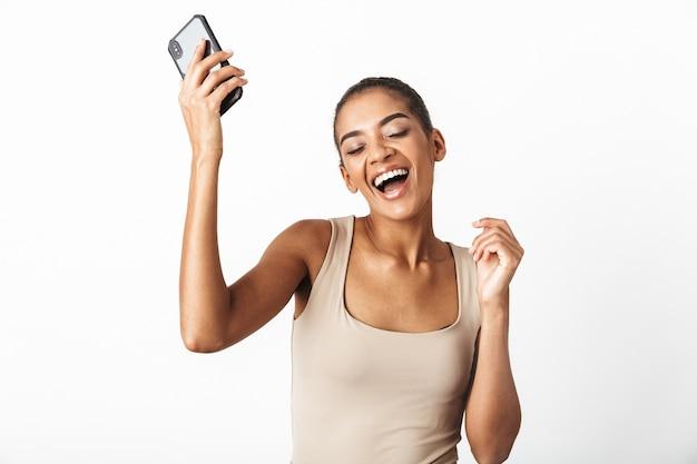Bela jovem africana vestida de forma casual, isolada, segurando o telefone celular, comemorando
