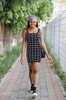 Bela jovem africana vestido elegante posando na rua. penteado afro