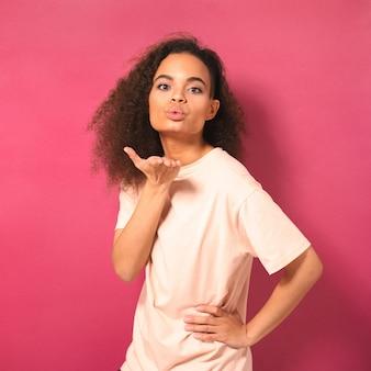 Bela jovem afro-americana com cabelo afro mandando beijos no ar, olhando positivamente para