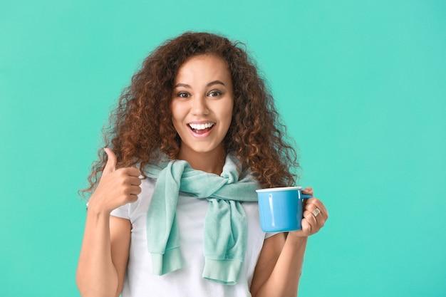 Bela jovem afro-americana com chá quente mostrando o polegar para cima na parede colorida