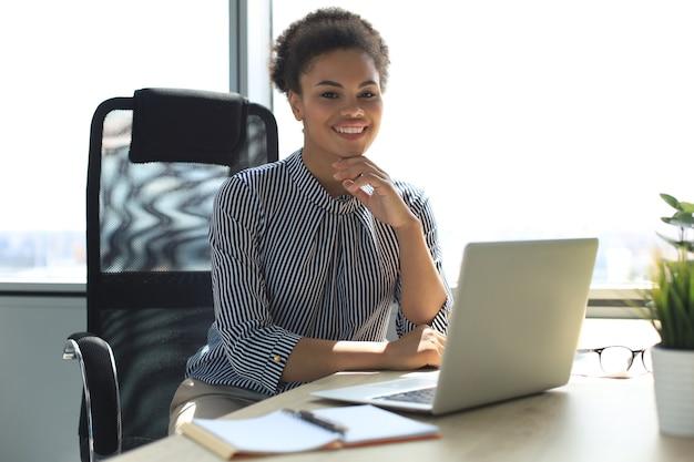 Bela jovem afro-americana está sentada no escritório e olhando para a câmera.